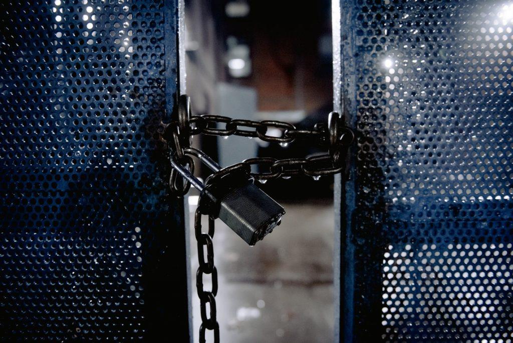 metal lock on blue gates on entrance of building